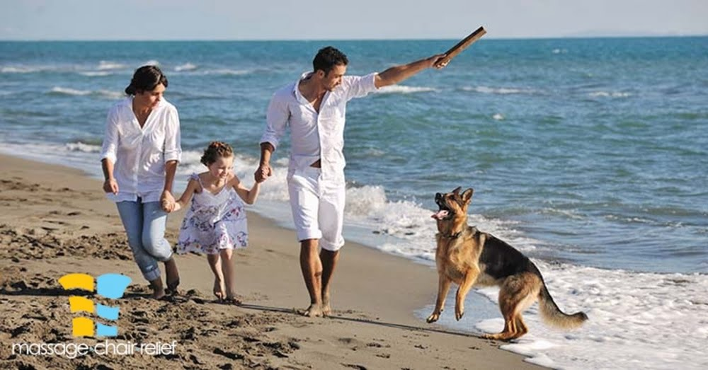 happy young family in white clothing have fun and play with beautiful dog at vacations on beautiful beach